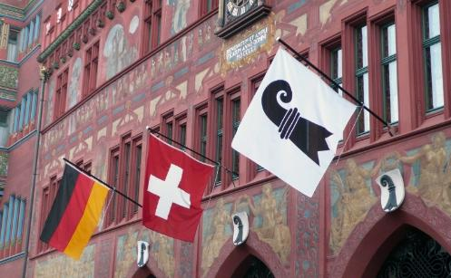 The Basel, Swiss and  German flags fluttering outside Basel City Hall.