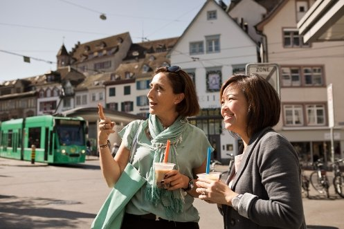 Two women from different backgrounds chatting on Barfüsserplatz in Basel.