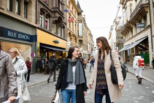 Two young women in good spirits walking along Freie Strasse in Basel.